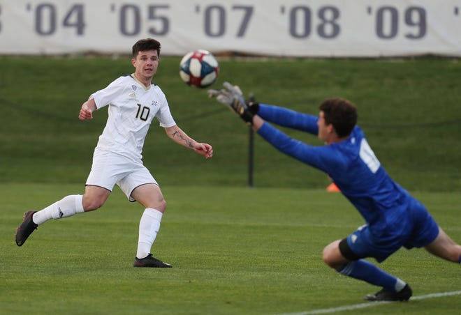 University of Akron's Colin Biros watches as Western Michigan University goalkeeper Isaac Walker makes a save on his kick during the first half of their soccer game at Cub Cadet Field on Wednesday. [Mike Cardew/Beacon Journal]