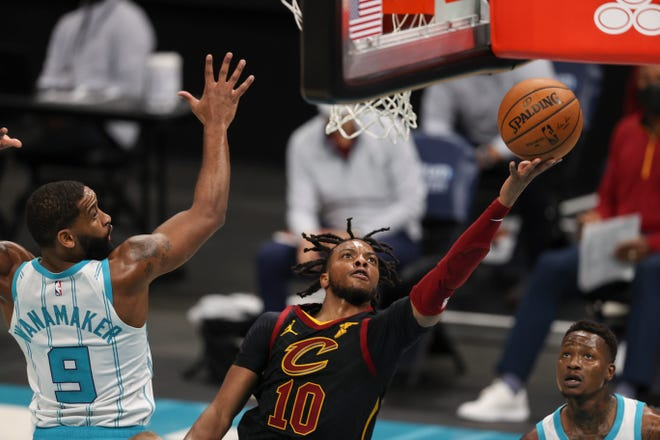Cavaliers guard Darius Garland (10) drives to the basket past Charlotte Hornets guard Brad Wanamaker (9) during the second quarter of the Cavs' 103-90 win Wednesday night in Charlotte. [Nell Redmond/Associated Press]