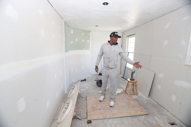 Geno Toney walks through the home he is rehabbing to house troubled youth in Akron.