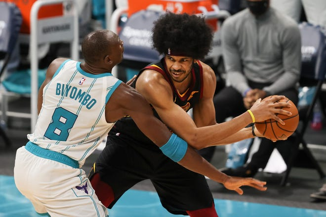 Cleveland Cavaliers center Jarrett Allen, right, looks to pass around Charlotte Hornets center Bismack Biyombo (8) during the second half of an NBA basketball game in Charlotte, N.C., Wednesday, April 14, 2021. (AP Photo/Nell Redmond)