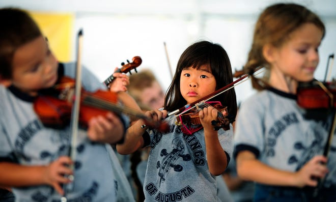 In this photo from 2011, Rachel Cain, 6, and dozens of other children from Suzuki Strings of Augusta perform during the Arts in the Heart Festival in Augusta.