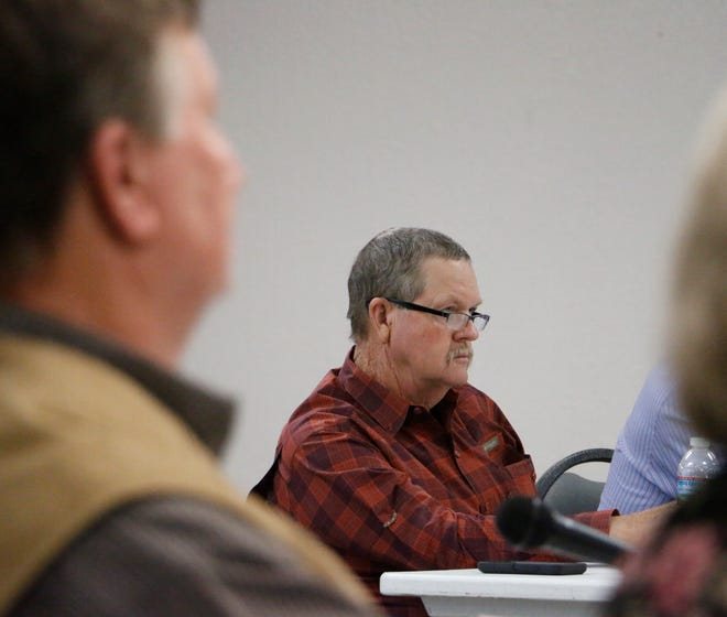 Brown County commissioners Gary Worley (foreground) and Larry Traweek listen to citizens' comments about the solar farm project Wednesday night at the Adams Street Community Center in Brownwood.