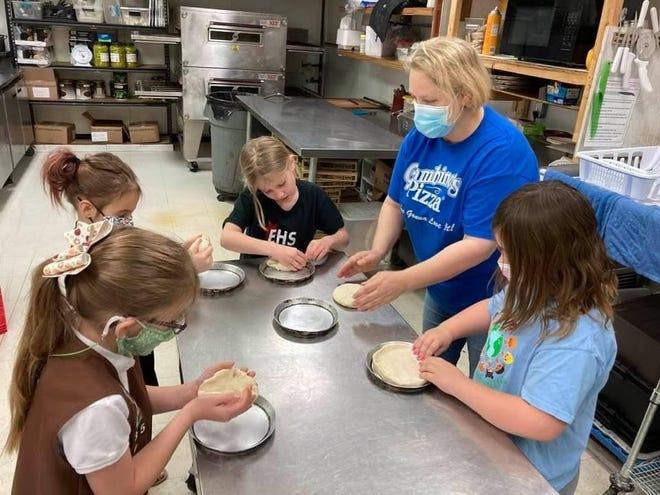 Gambino's Manager Toni White teaches Girl Scout Troop #41235 how to make a pizza.