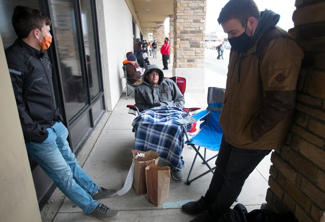 George Hinton, from left, Scott Strebig and Michael Sustar wait in line to buy graphic cards outside of Micro Center on Bethel Road before it opens at  10 a.m. April 14. They had been there since just after midnight.