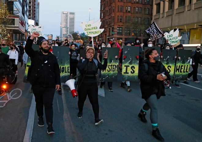 """Hana Abdur-Rahim, center, leads a group down W Board Street during the """"Stop the Lies"""" protest Wednesday evening in Columbus, Ohio on April 14, 2021.  Columbus police released additional information about some protesters who forced their way into police headquarters Downtown Tuesday evening."""