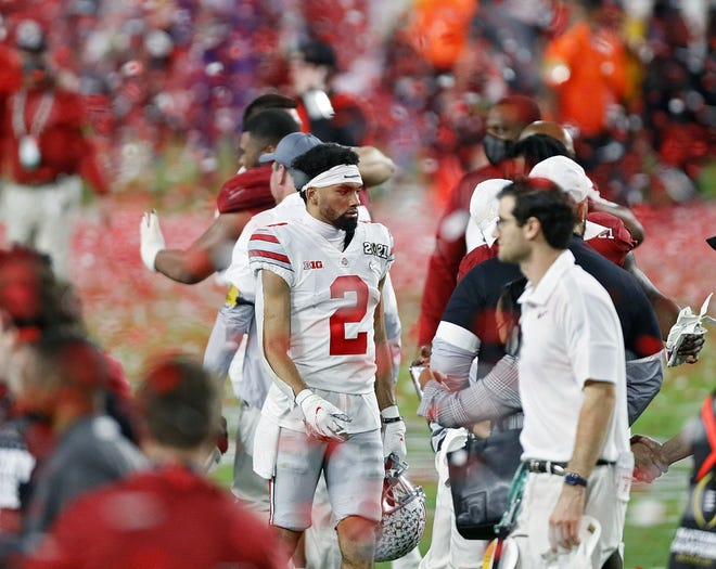 """Chris Olave walks off the field after Ohio State lost 52-24 to Alabama in the national title game Jan. 11. """"I had a terrible feeling in my stomach,"""" Olave said Thursday."""