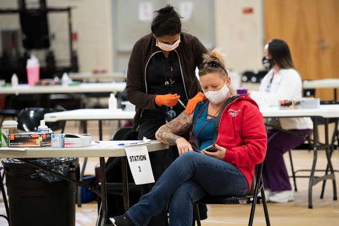 A Lake County school employee gets her vaccine for COVID-19 vaccine at Tavares High School. [Cindy Peterson/Correspondent]