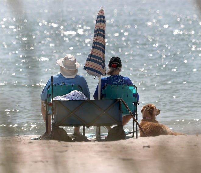 A couple and their dog relax after playing, Thursday April 15, 2021 on the Ponce Inlet dog beach in the Light House Point Park.