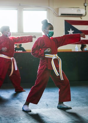 Naalah Borges, 10, of Brockton punches the air as she does a karate routine at Kenny's Karate School in Brockton on Wednesday, April 14, 2021.