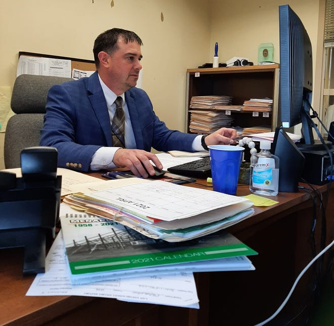 Stephenson County Assistant State's Attorney Tom Madigan reviews cases for the next day's docket in his office. Madigan spent almost 20 years as a police officer investigating and building criminal cases. Now he's the one prosecuting them.