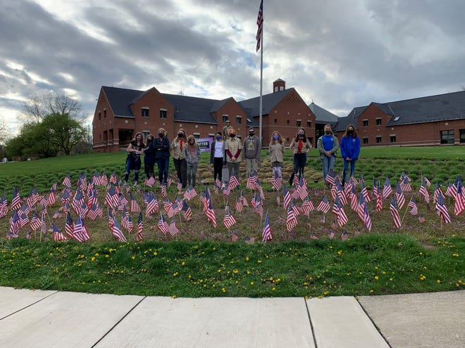 """BSA Girls Troop #7270 assisted Stow Arts Commission with placing flags that were """"planted"""" last fall at the Doughboy corner."""
