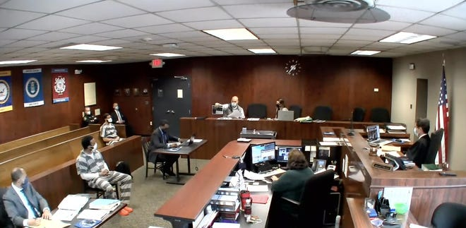 Monroe County Sheriff's Detective Sgt. Michael Preadmore presents photos of evidence taken from the scene of a Feb. 1 shooting on Stewart Rd. It was the third day of the preliminary examination. Photo of courtroom taken with permission from First District Court.