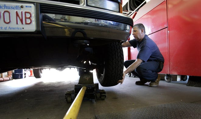 Mechanic Stan Pappastratis lifts the front end of a car to check its steering at Gulf Gas Station on Church Street in Pembroke.