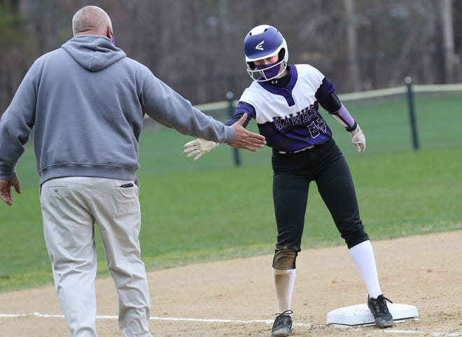 Marshwood's Shelby Anderson gets a high-five from her coach Peter Eastman after hitting a triple in Thursday's softball game against rival York. The Hawks opened the season with a 13-0 win.