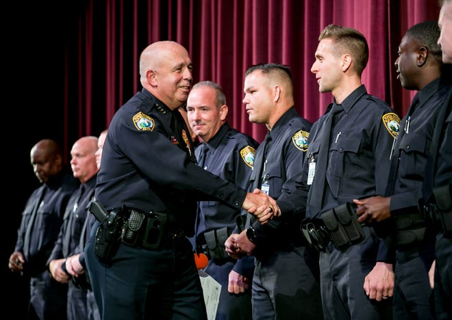 Chief Frank Kitzerow shakes hands with Nicholas Alonso after swearing in 11 new Palm Beach County school district officers at Palm Beach Central High School on Friday, August 9, 2019.  [RICHARD GRAULICH/palmbeachpost.com]