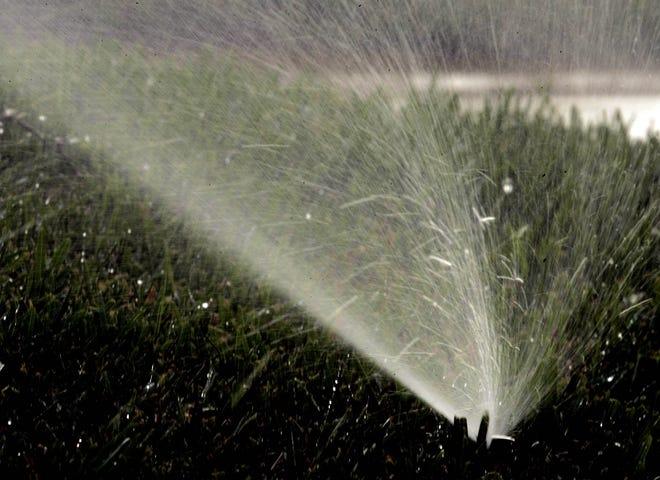 A sprinkler waters a lawn.
