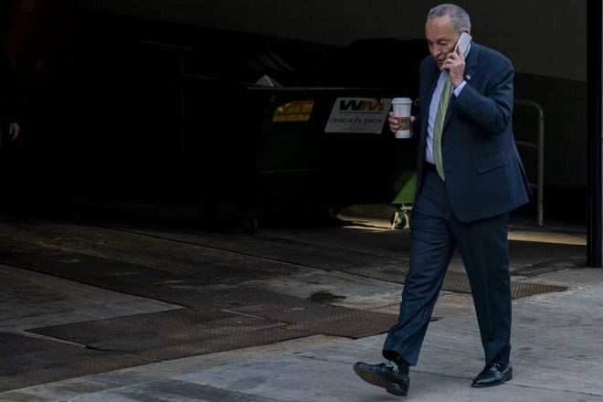 Senate Majority Leader Sen. Chuck Schumer of N.Y. speaks on the phone as he walks down a street downtown in Washington on Thursday. The Senate Parliamentarian's ruling on including the minimum wage in the American Rescue Plan was a setback for Schumer and progressive Democrats.
