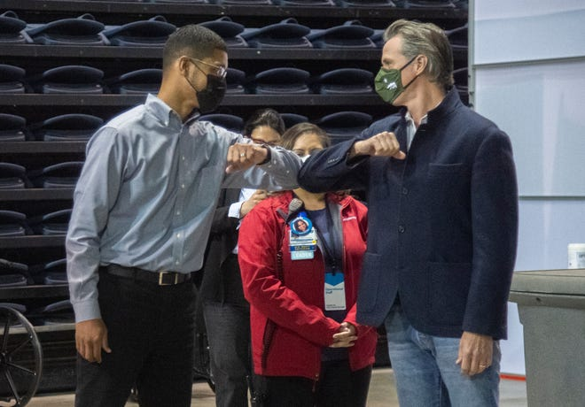 Gov. Gavin Newsom, right, gives an elbow bump to Stockton Mayor Kevin Lincoln before starting a tour of the Stockton vaccination hub at the Stockton Arena in downtown Stockton on Thursday, April 15 2021.