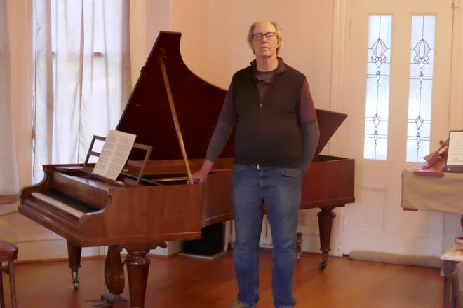 Mike Reiter stands in front of his Streicher piano.