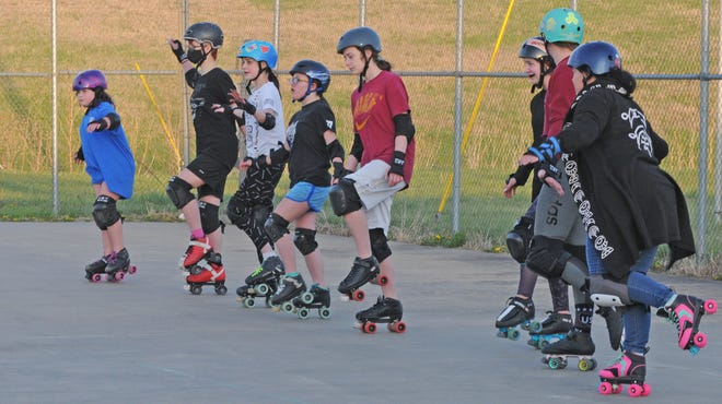 Young skaters practice balancing on one foot during and exercise at the outside skating with the Salina Sirens at the Quality Inn & Suites, 2110 W. Crawford St., tennis courts on Wednesday evening.