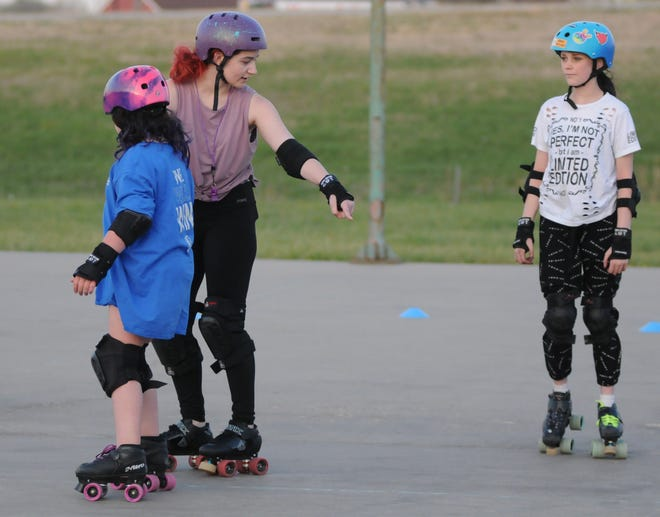 Coach Lainey Valentine instructs Kiera Wilson, 10, and Meadow Rowson, 15, during the free skate with the Salina Sirens at the Quality Inn & Suites outside tennis courts on Wednesday evening.