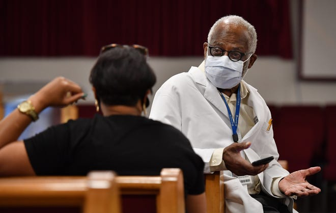 Dr. Washington Hill speaks to a woman who received her first COVID-19 vaccination during a vaccination clinic held Wednesday, April 14, 2021, at Bethlehem Baptist Church on 18th Street in Sarasota. Hill was present to answer any medical questions people might have about the vaccine.