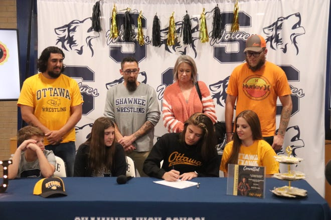 Shawnee High School senior wrestler Jordan Lomeli (seated second from right) signs a national letter of intent to wrestle for Ottawa University in Kansas. Lomeli is a two-time state qualifier and West Regional champion. Seated from left are Jordan's brother Gage, sister Megan and mother Melissa. Standing from left are Jordan's father and Shawnee assistant coach Justin Lomeli, Shawnee assistant coach Andrew McCune, grandmother Mariam Bender and uncle Robert McKinney.