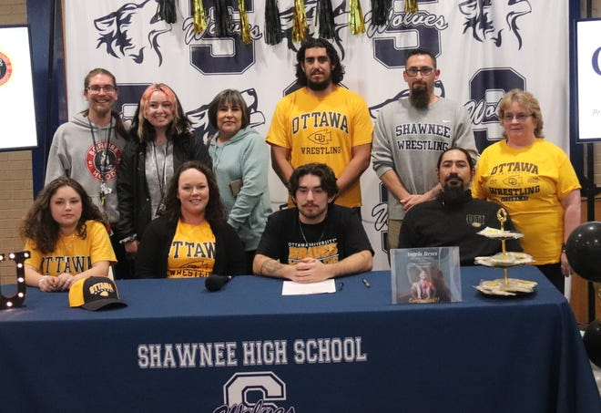 Shawnee High School senior wrestler Angelo Reyes (seated second from right) signed a national letter of intent to wrestle at Ottawa University in Kansas. Reyes was a two-time state qualifier for Shawnee. Seated with Angelo from left are Angelo's sister Emmie, mother Becki and father Chain. Standing from left are brother in law Caiden Reyes, sister Shyann; grandmother Sharon, Shawnee assistant coaches Andrew McCune and Justin Lomeli and grandmother Brenda Hutchcraft.