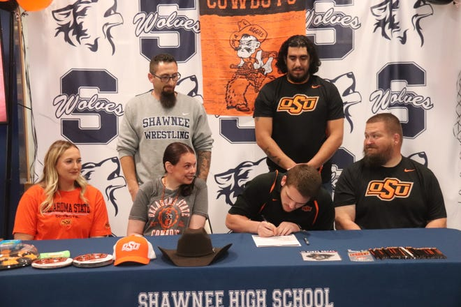 Shawnee High School senior wrestler Austin Long (seated second from right) signs a national letter of intent to wrestle at Oklahoma State University next season. Long was a regional champion and state qualifier for the Wolves this past season. Seated from left are Austin's sister Katie, mother Heather and father James. Standing from left are Shawnee assistant coaches Andrew McCune and Justin Lomeli.