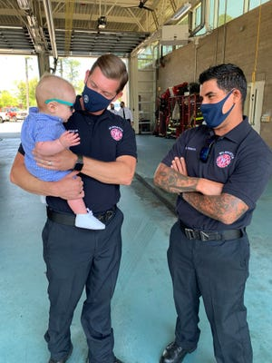 Firefighter Josh Gibson holds baby Harris as firefighter Eli Venecia looks on. Gibson and Venecia are credited with saving Harris' life.