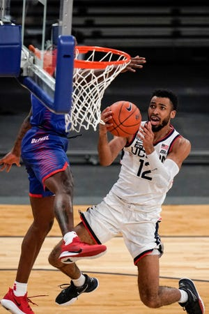 Connecticut's Tyler Polley drives past DePaul's Romeo Weems during the Big East tourney in New York.