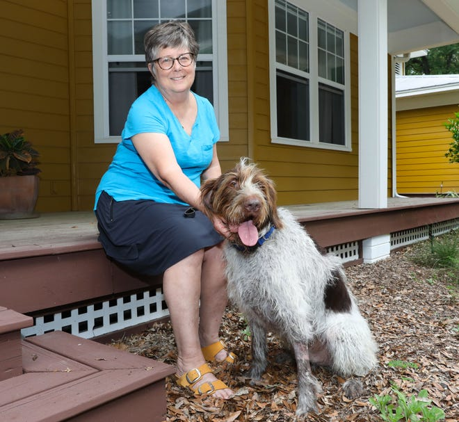 "Bonnie Josey and her dog Toby, a German wirehaired pointer, are shown Thursday at their home in High Springs. Josey was locked out of her car and stranded along Interstate 75 during a storm last Saturday night in Gainesville. ""It was a terrifying night,"" she said."