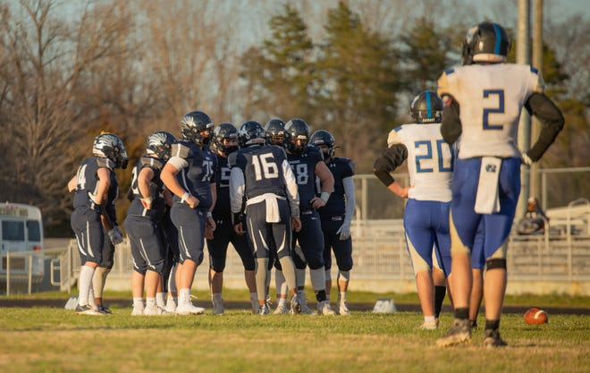 Western Alamance senior quarterback Kendall McKoy, middle, huddles with the Warriors offense before a snap against McMichael.