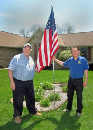 Members of the New Philadelphia Rotary Club place flags throughout the city as a part of the club's Salute Freedom Program.