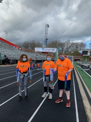 Thunder Valley Pioneers 4-H Club members worked at the finish line for a half marathon race and handed out race medals and snacks. Pictured, from left: Jordyn Thomas, Gaven Norman and Drew Long.