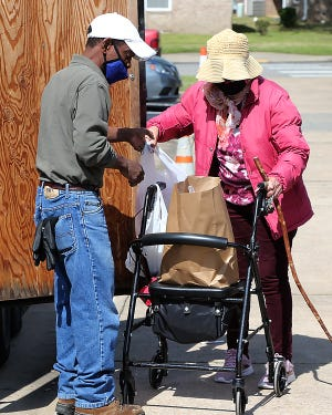Antioch for Youth & Family volunteer, Fred Perkins, left, helps distribute bags of groceries to low-income elderly, disabled and struggling families, Thursday, April 15, at the Nelson Hall Beckman Center, 2100 N. 31st St., in Fort Smith.