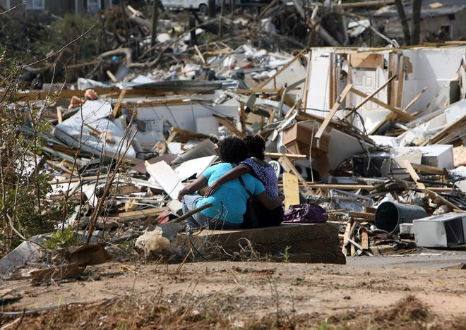 Twins Janece Maze, left, and Janeka embrace as they look at debris in Alberta City left by last week's tornado Thursday, May 5, 2011. Janece, a law student at the University of Alabama, lived in Arlington Square Apartments. (Staff file photo)