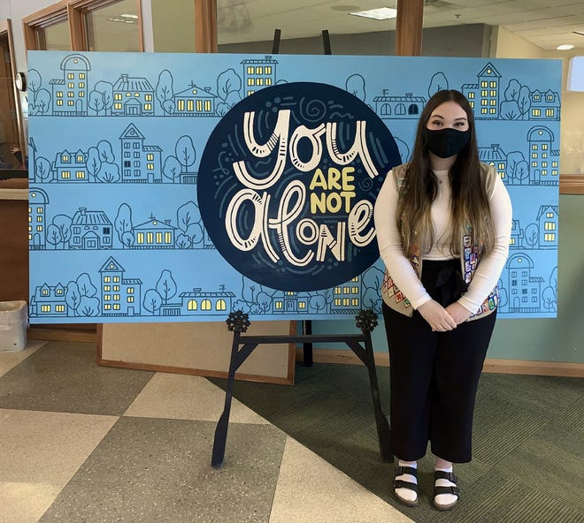 Thomas Worthington High School junior Andrea Nadolny stands next to her suicide-awareness mural currently on display at the Community Center, 345 E. Wilson Bridge Road. Another mural is planned for this summer at the Old Worthington Library, 820 S. High St.