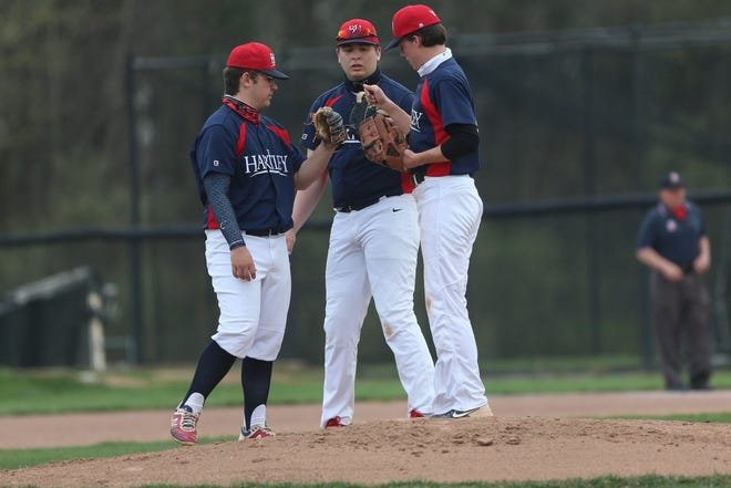 Hartley's Dimitri Boumis (left), Jake Skelly and pitcher Emmett Gillies meet on the mound April 5 against Reynoldsburg. The Hawks rallied from a 5-0 deficit to beat the Raiders 17-6.