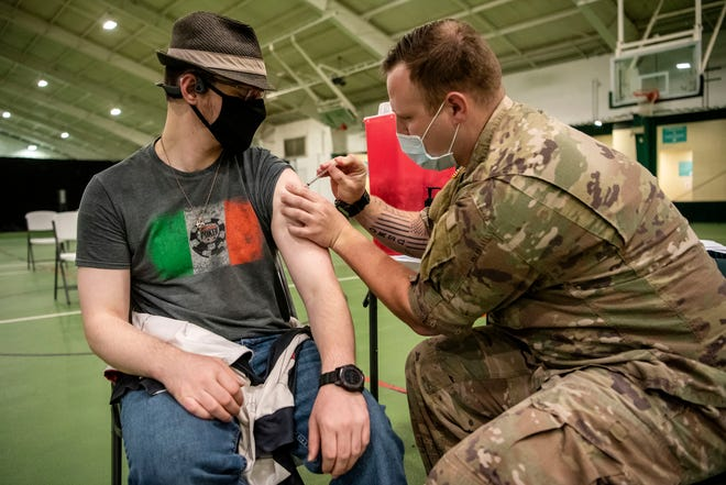 Spc. Joseph Gross administers the Pfizer-BioNTech COVID-19 vaccine to Adam Young during a walk-in clinic on Thursday, April 15, 2021 at the YMCA Multi-Sports Complex in Battle Creek, Mich.