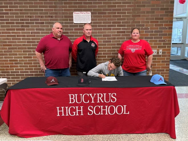 Bucyrus' Kael Scott signs his letter of intent to play baseball at Adrian College.  (L to R): dad Travis, coach Sean Maudsley, Kael, mother Stephnie