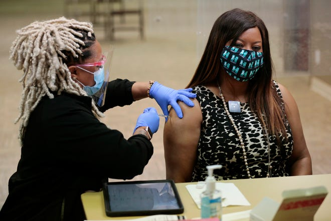 Hamilton County Commissioner Alicia Reece receives her first dose of the Pfizer COVID-19 vaccine in a shot administered by nurse Kenyatta Stewart from Cincinnati Public Health during a walk-up vaccine event at the Hamilton County Board of Elections in Norwood, Ohio, on Thursday, April 15, 2021.
