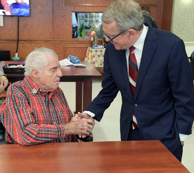 Gov. Mike DeWine visits with Pearl Harbor vet Joe Whitt, who died on Wednesday at the age of 97.
