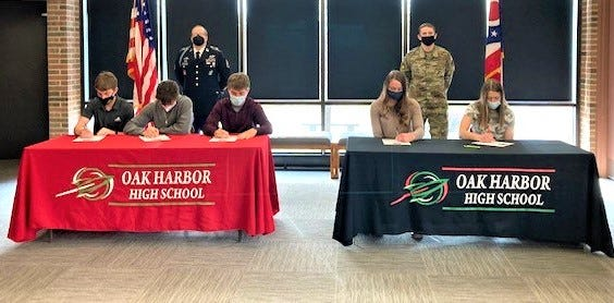 At the red table are in front left to right, Ryan Friar, Army ROTC; Joseph Perry, Marines; and Eli Sherman, Army Reserves. At the black table are AunaTack, Ohio Air National Guard; and Madison McKitrick, Ohio National Guard. In back are Sgt. Blankenship, U.S. Army military recruiter and Sgt. Gainer, Air National Guard recruiter.