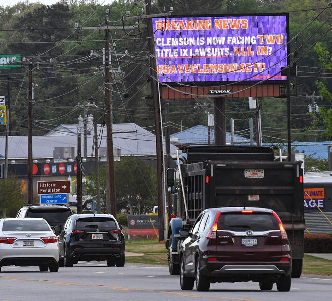 "A billboard along US76 Highway in Pendleton flashes ""Breaking News   Clemson is now facing two Title IX lawsuits. All In? #SaveClemsonXCTF"""