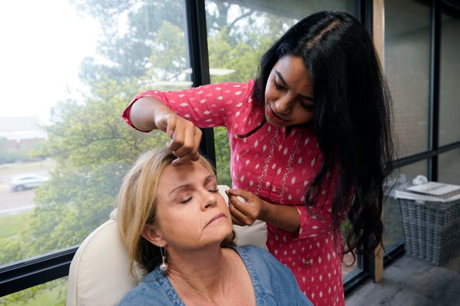 Eyebrow threader Dipa Bhattarai demonstrates eyebrow threading, the technique of using a single strand of cotton thread to remove hair, on Betty Tucker, of Madison, Wednesday, April 14, 2021, in Madison, Miss. Mississippi no longer requires professional licenses for people who offer low-risk beauty services, such as eyebrow threaders, eyelash technicians or makeup artists, a change that will save residents thousands of dollars and hours of time spent on training.