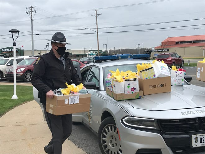 Trooper Kevin Beringo of the Mansfield Post of the Ohio Highway Patrol unloads boxes earmarked for residents of Elmcroft in Ontario Thursday. The boxes contained cards from Ontario Stingel Elementary School students who wrote to the senior citizens during the coronavirus pandemic.