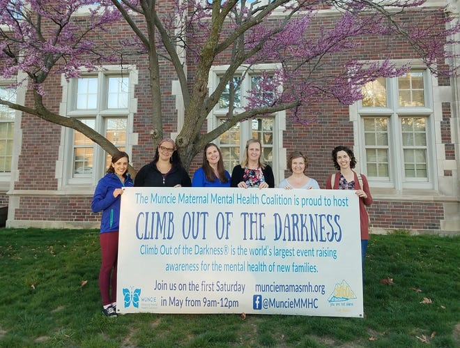 "Members of the Muncie Maternal Mental Health Coalition standing with a sign they created for the ""Climb Out of the Darkness"" event, scheduled for May 1."