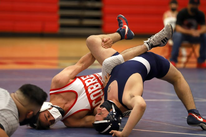 Wildcat Manny Lucero bridges to keep his shoulders off the mat in his 152-pound bout against Cobre's Esteban Molina.