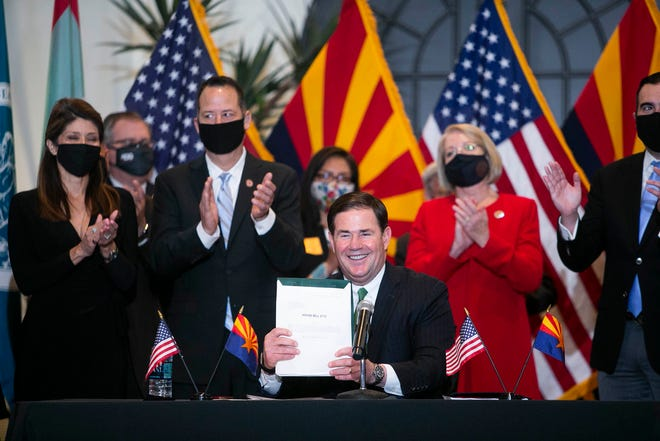 Gov. Doug Ducey holds up HB 2772 after signing it in the Steele Auditorium at the Heard Museum in Phoenix on April 15, 2021.